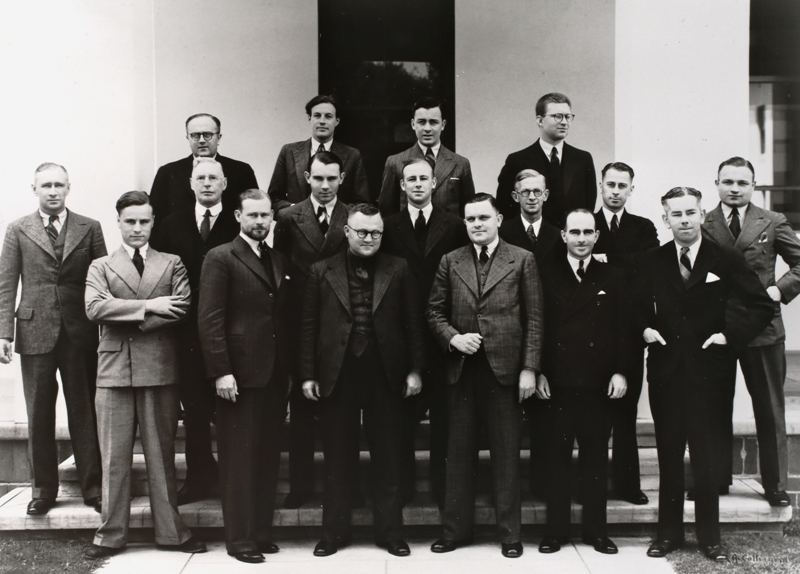 Federal Parliamentary Press Gallery, December 1937. Absent: J A Alexander (Melbourne Herald), H Marshall (Melbourne Herald), E H Cox (Argus), J M Stanley (Sydney Telegraph), L F McDonnell (Brisbane Telegraph), F B Tremearne (Australian United Press), L Thomas (Australian United Press). Back row: L R McLennan (Argus), J E Mitchell (Sydney Morning Herald), K Murphy (Melbourne Herald), S Speight (Sydney Morning Herald). Middle row: E McLoughlin (Sydney Morning Herald), W F Whyte (Federal News Service), A Richards (Sydney Sun), H Austin (Age), L Palmer (Canberra Times), H Taperell (Australian United Press), R B Leonard (Sun Pictorial). Front row: D Wilkie (Melbourne Herald), O G Olsen (Sydney Sun, Gallery President), W E Denning (Australian United Press), B J Anderson (Melbourne Herald), M Byrne (Sydney Sun), D K Rodgers (Labor Daily).
