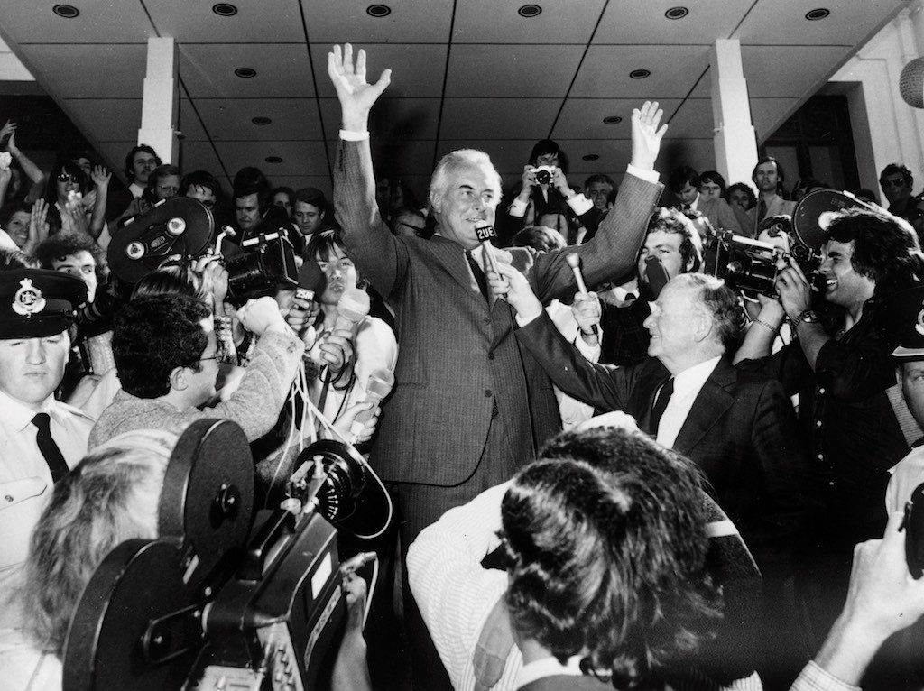 The biggest day in Australian political history, 11 November 1975. Prime Minister Gough Whitlam waves to the gathered crowd of supporters while a throng of Press Gallery media is there to record it. Note that the cameras are all shooting on film. The 2UE journalist would've recorded excellent audio at that distance, had Gough said anything.