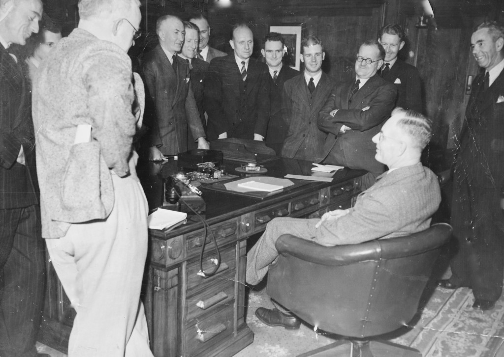 John Curtin Prime Ministerial Library. Records of the Curtin Family. Former journalist John Curtin meets the Canberra Press Gallery. (Known as The Circus) C.1945. JCPML00376/2. Curtin is seated and standing, from left to right, are Don Whitington (Daily Telegraph), Ross Gollan (Sydney Morning Herald), John Corbett (Argus), Frederick Smith (Australian United Press), Richard Hughes and Norman Kearsley (Brisbane Telegraph), T L Thomas (Australian United Press), Ted Waterman and Joe Alexander (Melbourne Herald), Jack Commins (Australian Broadcasting Commission) and Don Rodgers (Curtin's press secretary). This copy courtesy of the Reid family collection.