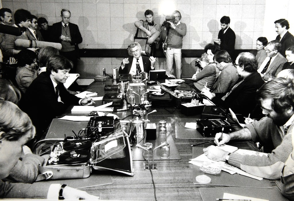 Prime Minister Bob Hawke speaks at a press conference in front of a number of radio reporters with both Nagra reel-to-reel and the more modern cassette recorders. The cameraman behind Hawke is shooting on U-matic, a large and cumbersome format where the camera was connected by cable to the recorder (which housed the tape).
