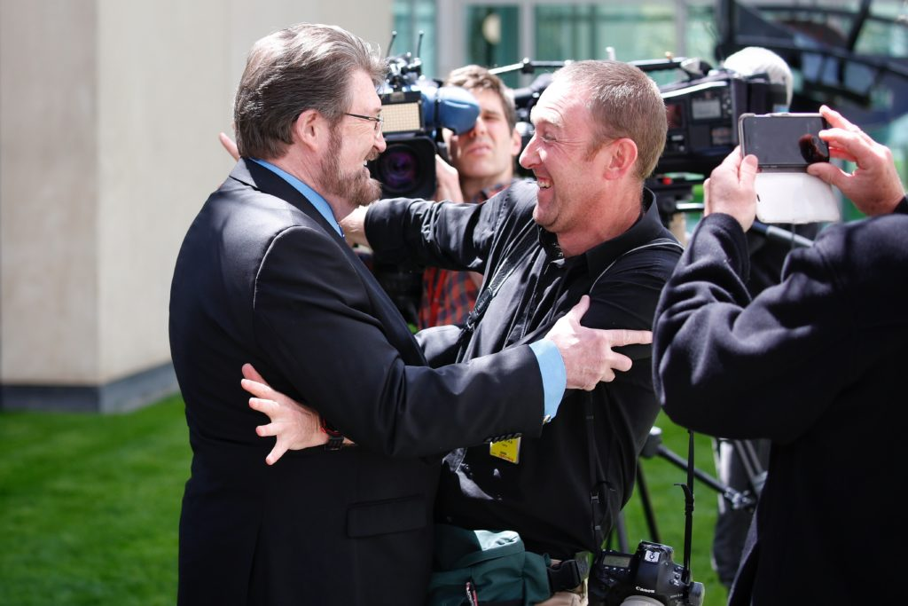 Senator Derryn Hinch and Press Gallery President Andrew Meares embrace, surrounded by cameramen and photographers.